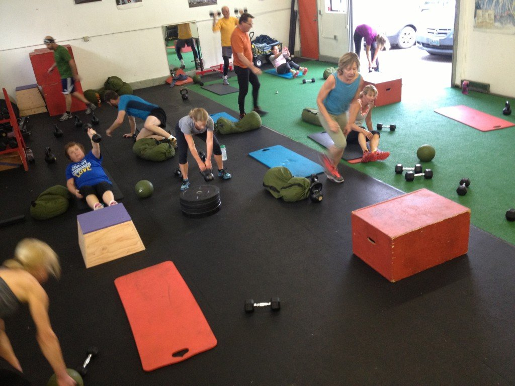 815 class working hard through sandbag get-ups, swings, push press, lateral hops and single arm sit-ups